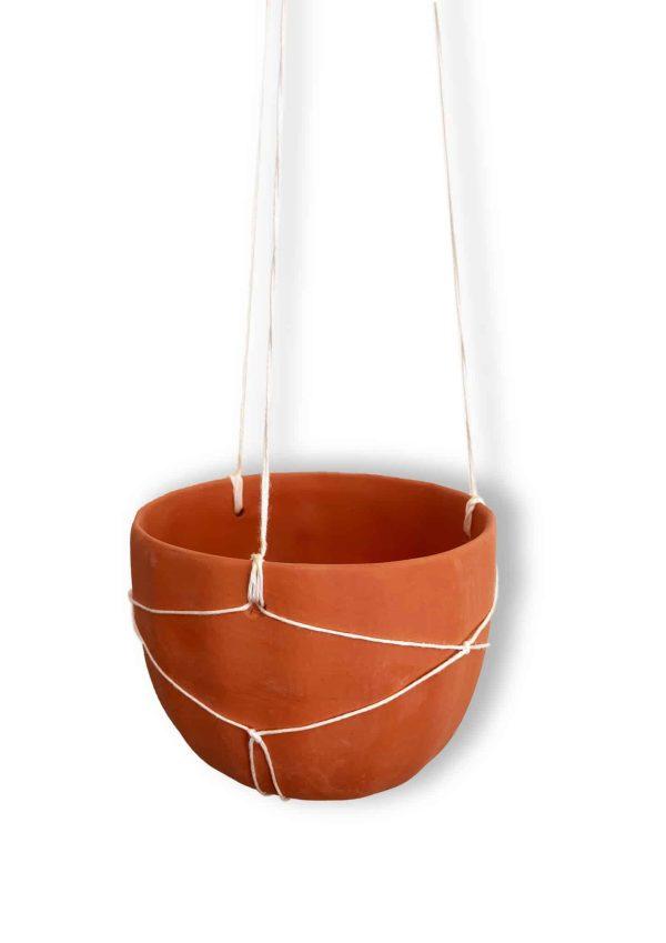 Un pot en terre cuite suspendu, en macramé, sans plante verte à l'intérieur