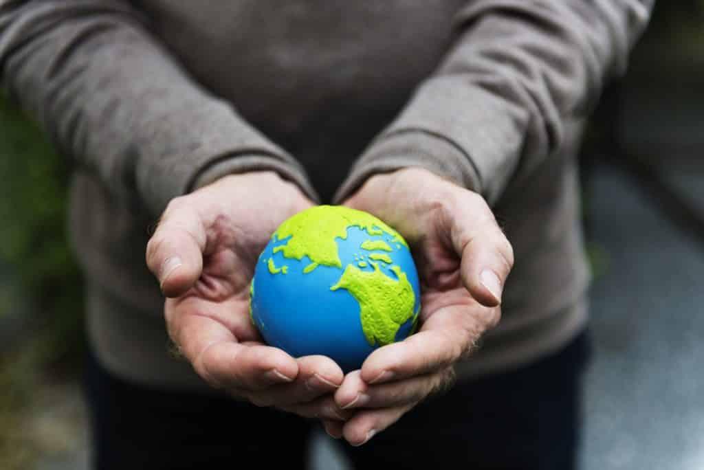 homme tenant un globe terrestre concept écologie