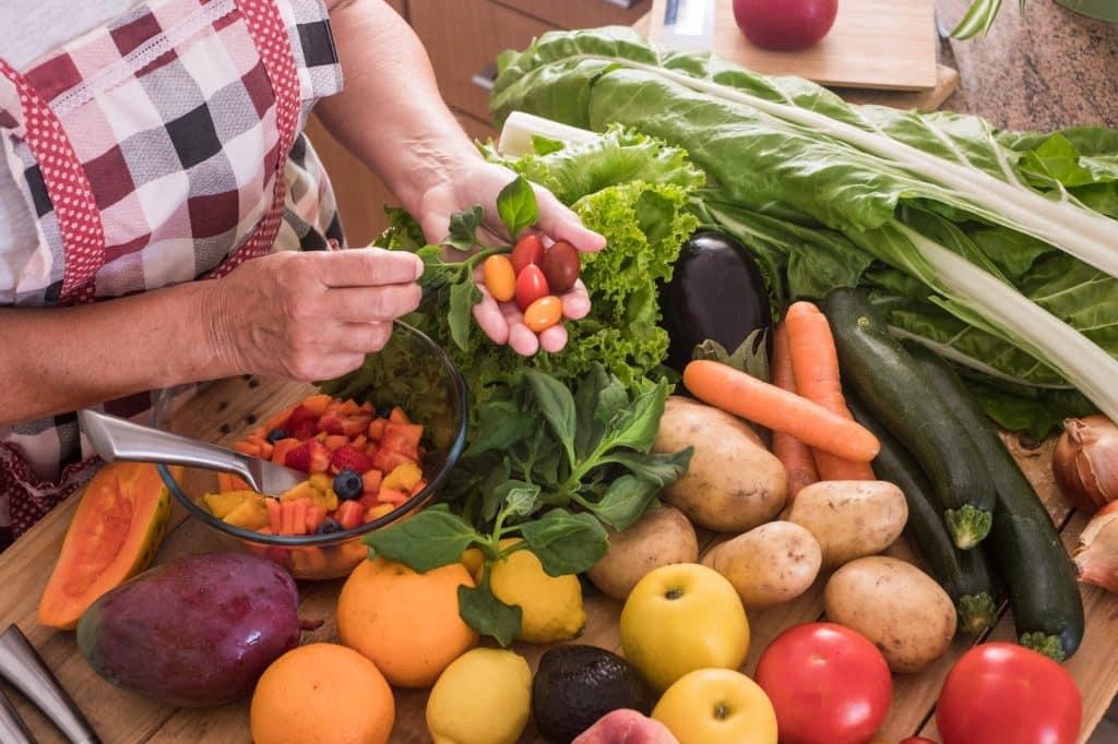 femme coupe des fruits et légumes